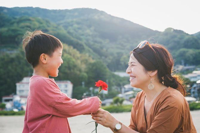 母親にカーネーションの花を手渡す少年