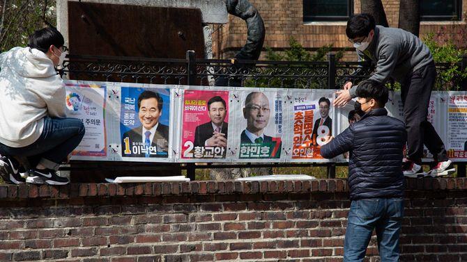 韓国・ソウルで選挙ポスターを貼る国政選挙委員会の関係者たち=2020年4月2日、来る総選挙に向けた13日間の公式選挙運動期間が4月2日から始まった。