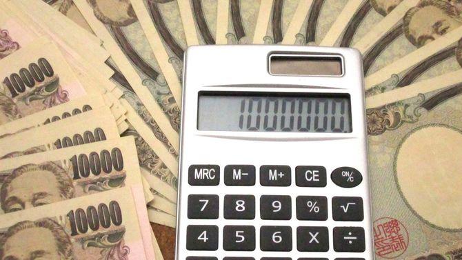 大量の一万円札の上に置かれた電卓の表示には100万