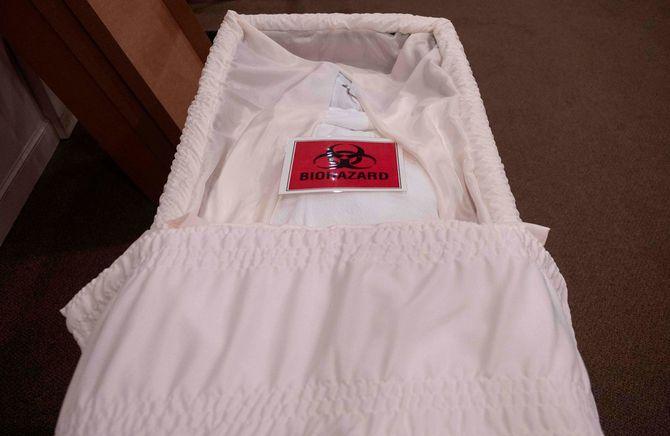 棺に入れられたCOVID-19の犠牲者の遺体にバイオハザードのサインが見られる。2020年5月1日、メリーランド州
