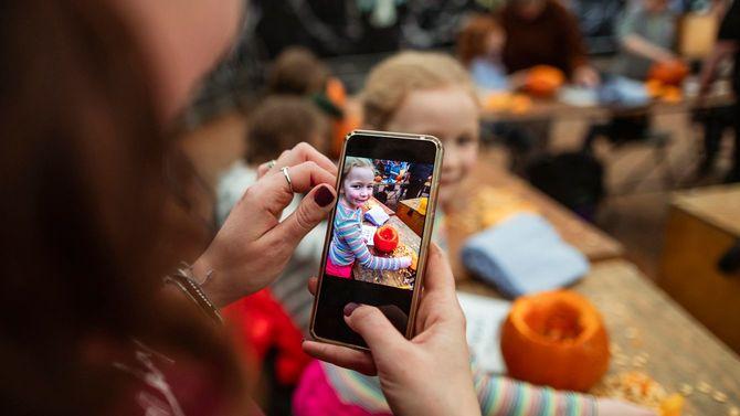 iPhoneで子どもの写真を撮影する母親
