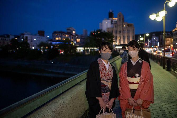 夜の京都でマスクをつけ橋の上に立つ着物を着た日本の女性二人