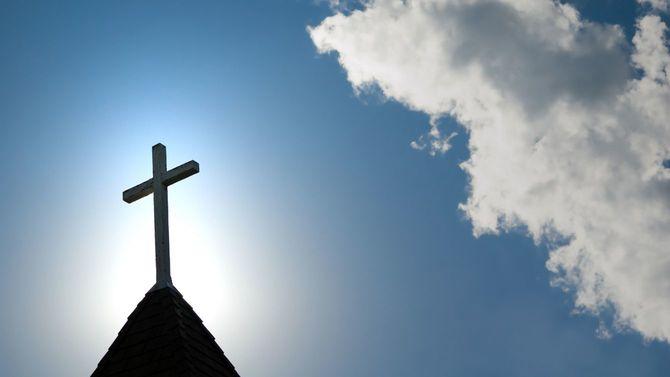逆光を受けた古い教会の十字架