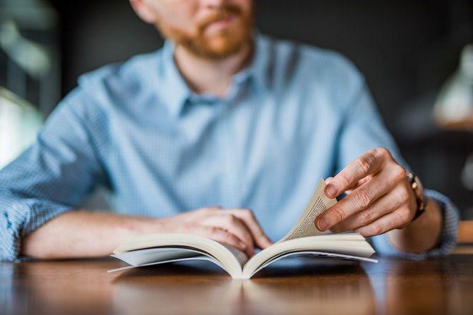 本の手を読んでいる若者が間近に