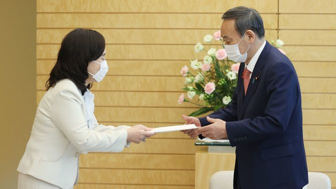 人事院の一宮なほみ総裁(左)から勧告を受け取る菅義偉首相=2020年10月7日、首相官邸