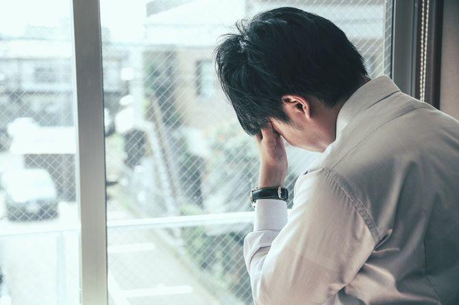 窓辺で頭を抱える男性