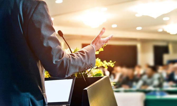 会議場で聴衆の前で演説をするビジネスマン