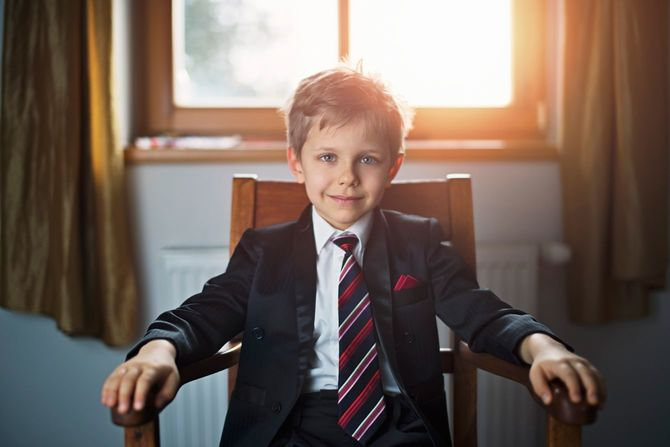 スーツを着て部屋の肘掛け椅子に堂々と座る子ども