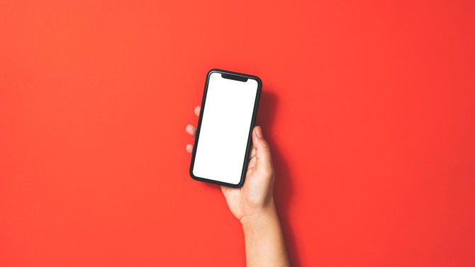 赤い背景にスマートフォンを持つ手