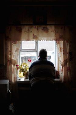窓辺で外を眺める高齢男性