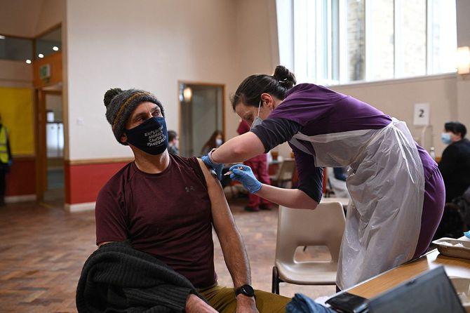 英中部シェフィールドで新型コロナウイルスのワクチン接種を受ける男性(左)