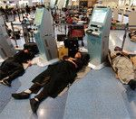 運行再開を待ち駅構内で休む人々。JR東日本は早々に完全運休を発表、他社は5月雨式に間引き運転を再開した。(Gettyimages=写真)