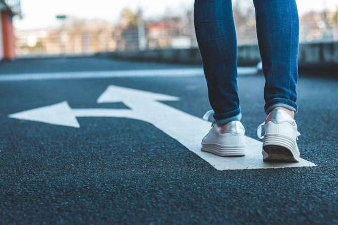 道路標識の分かれ道の前に立つ人