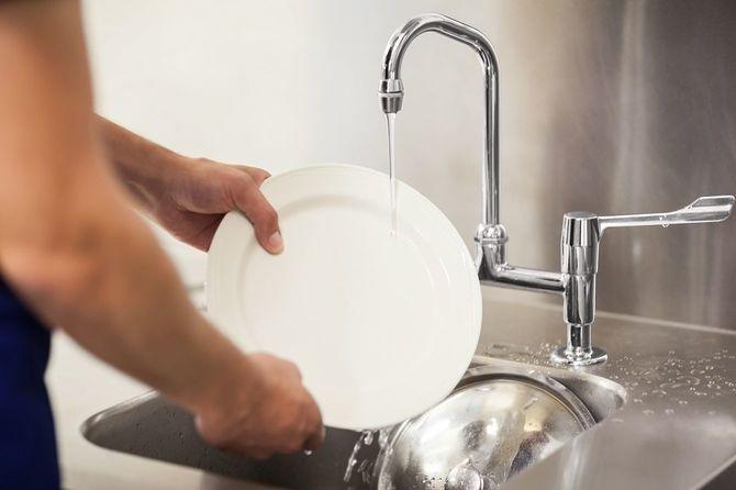 シンクで皿洗いをしている男性