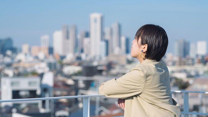 若く、自信のある若いビジネスウーマンが、屋上から東京を見渡す