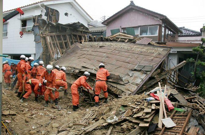 倒壊した家屋の下に、行方不明者がいないか捜索する消防隊員