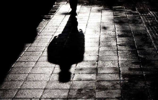 道を一人で歩く人の影
