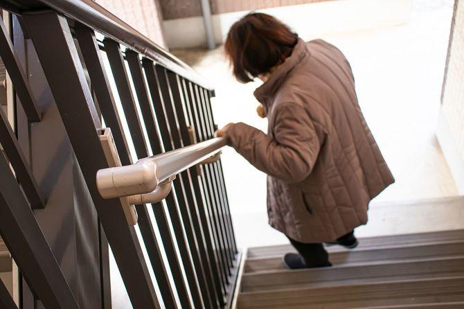 手すりを持ち、階段を降りる年配の女性