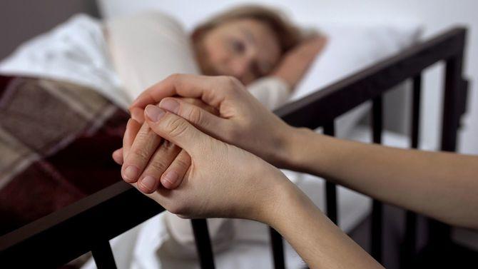 終末期患者と手を握る家族