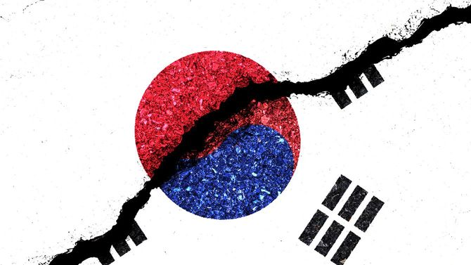 亀裂の入った壁に描かれた日章旗と、韓国の国旗