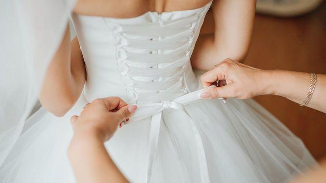 花嫁介添人がウェディングドレスの花嫁のコルセットをちょうちょ結びで締めている