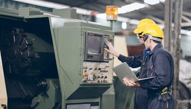 工場で機械をチェックする2人の技術者