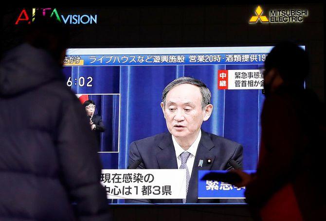 新型コロナ感染症 緊急事態宣言を再発出/スクを着用した通行人は、ビルの大型スクリーンに映し出された菅義偉首相の生中継を見ている=2021年1月7日