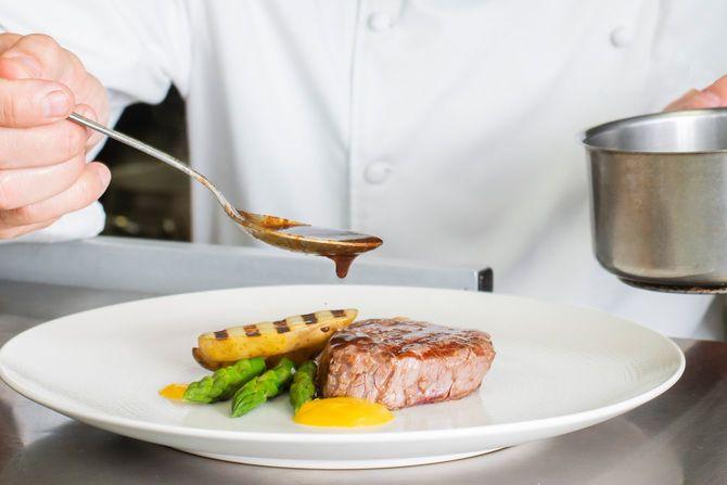 高級ステーキに手づくりソースをかけるシェフ