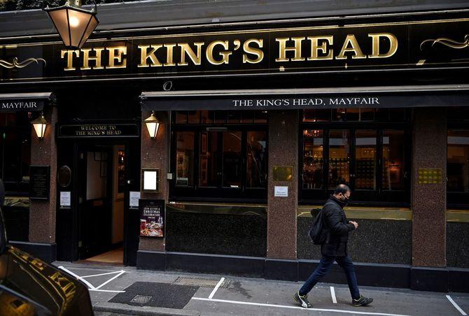 イギリスのパブ「The Kings Head」の前を通り過ぎる市民(2020年11月3日、ロンドン)