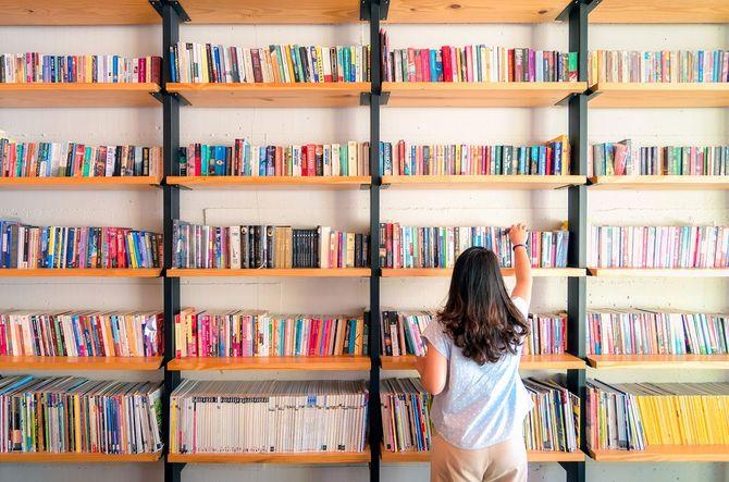 本棚から本を選ぶ女性