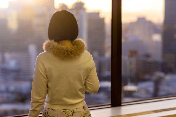オフィスの窓から高層ビル群を眺める女性の後ろ姿