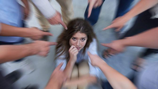 同僚から隠れようとする若い女性
