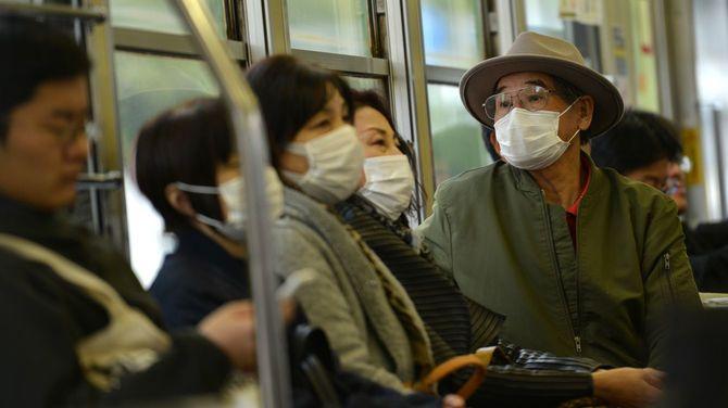 晴れた日の東京を走るバスの乗客たちがマスクを着けている