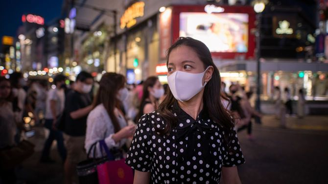 夜のスクランブル交差点を歩くマスクを着用した若い女性