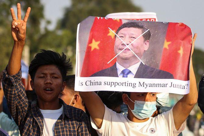 ミャンマーで行われた軍事クーデターに対する抗議デモで、中国習近平国家主席の写真入りプラカードを掲げ、国軍を支援しているとされる中国政府に抗議する参加者ら=2021年2月11日
