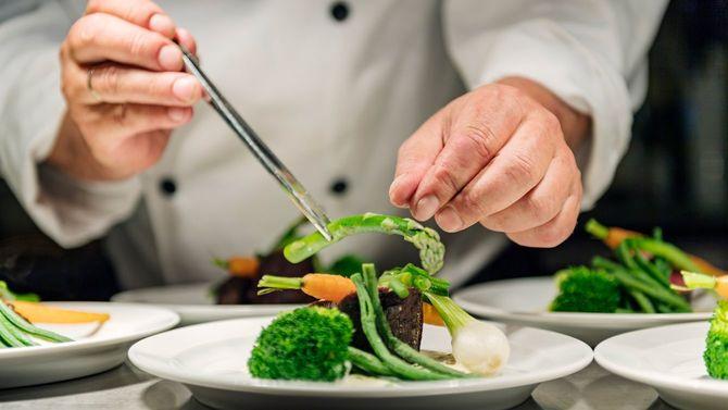 シェフが季節の野菜盛りにアスパラガスを添えようとしている