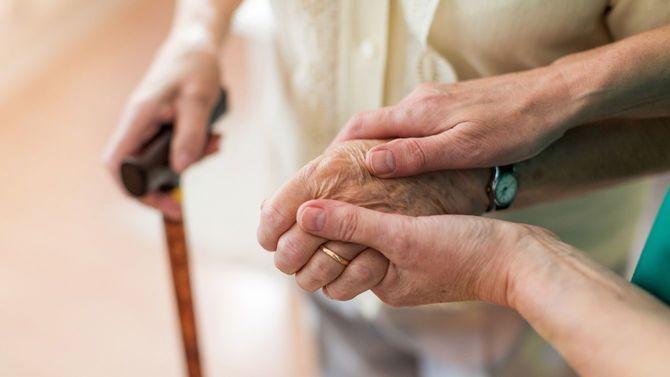高齢者の手を握る看護師の手元