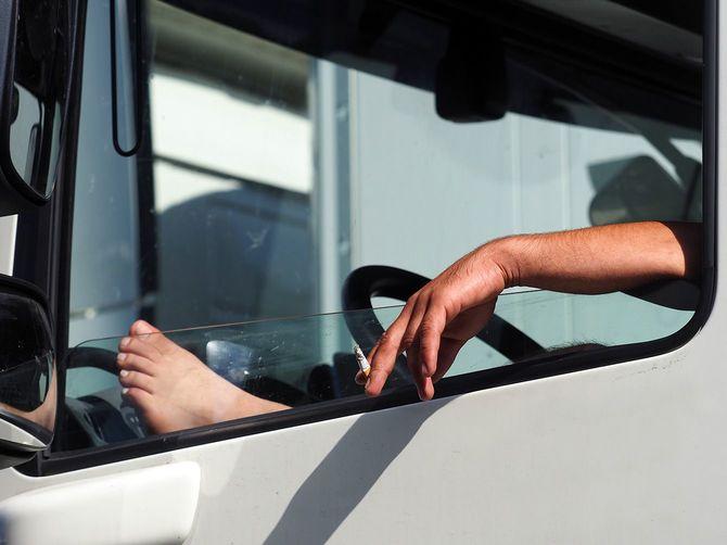 運転中に喫煙トラック運転手、素足、窓を開きます。交通渋滞中にリラックス、休憩