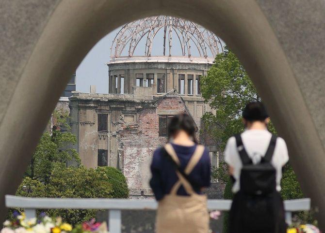 原爆が投下されて75年となる「原爆の日」を前に、原爆死没者慰霊碑に手を合わせる人たち。奥は原爆ドーム=2020年8月5日午前、広島市中区
