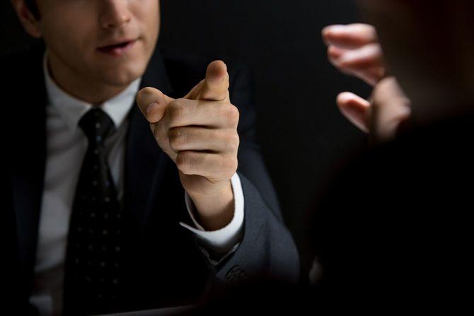 容疑者取り調べ中に指をさして指摘する検事の男性