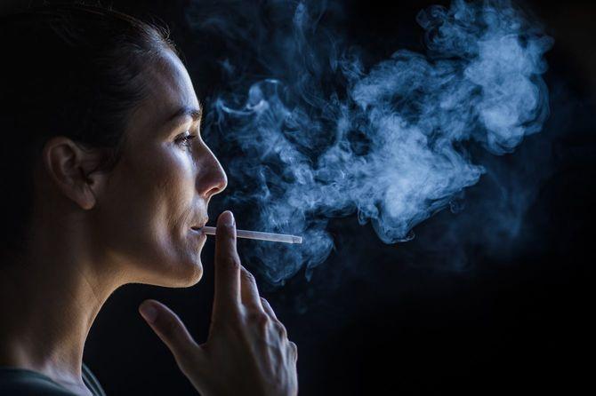 暗闇の中で喫煙する美人のプロフィールビュー。
