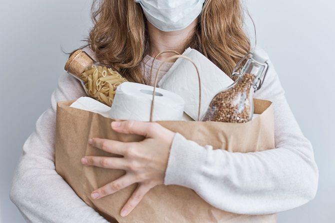 コロナウイルスcovid-19コンセプトに関する消費者の購入パニック。スーパーマーケットのコンセプトで一括で必需品を購入する人々。女性はトイレットペーパー、パスタ、バックウィート
