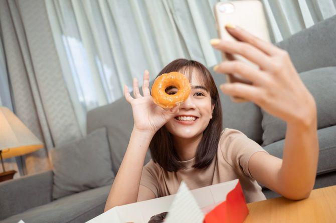 ドーナツを目に当てて自撮りする女性