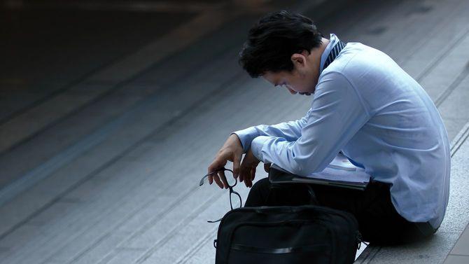 ストレスのたまった男性が階段に腰を下ろす