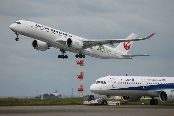 離陸する日本航空(JAL)機(上)。右下は全日本空輸(ANA)機=2020年10月18日、東京・羽田空港