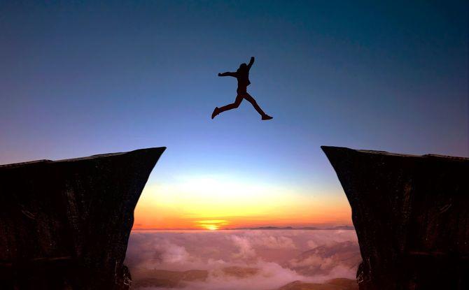 ジャンプで崖を渡ろうとする人