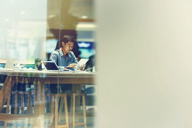 アジア系のビジネスマンが会議室での作業