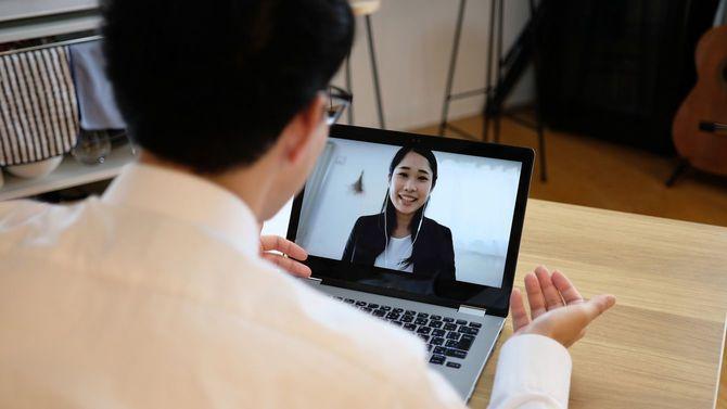 ウェブ会議で同僚と話すアジアのビジネスマン