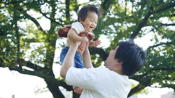 父親がたかいたかいをして笑顔がはじける赤ちゃん