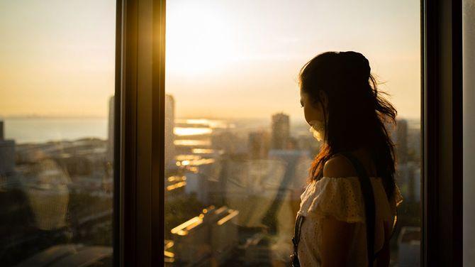 窓から夕日を見ている女性